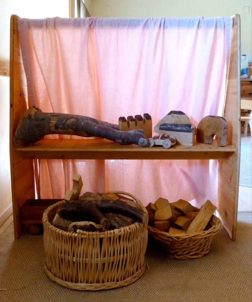 Foto von einem Spielspänder mit den für Waldorfkindergärten typischen Holzspielsachen